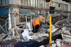 A local council worker surveys damage to a building in central Christchurch after the earthquake. Photo / Simon Baker