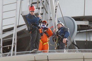 Skywalk staff talk to the man (centre, in orange) who was threatening to jump off the Sky Tower. Photo / Brett Phibbs