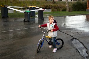 Michael Walker, 4, rides past the hole which he fell into after he 'zipped away' from his dad. Photo / Simon Baker