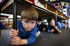 Lachlan Botting (front) and his classmates shelter under tables during an earthquake drill. Photo / Alan Gibson
