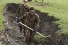 Soldiers working in a hole in the ground alongside the Kaiapoi River. Photo / Mark Mitchell