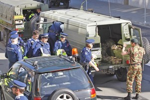 Police officers are loaded into NZ Army vehicles outside the Christchurch central Pplice station, bound for Burnham military camp. Photo / Sarah Ivey