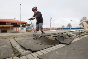 Anthony Krom, aged 10, attempts to ride his scooter over an earthquake damaged footpath in Kaiapoi. Photo / Mark Mitchell