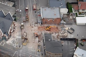 Aerial photograph of construction equipment cleaning up the remains of a demolished building on Victoria Street in central Christchurch. Photo / Sarah Ivey