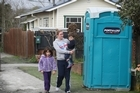 Avonside resident Lisa Booth walks with Hadas Livne (6) and Ronnie (3) walks past a port-a-loo in the suburb. Photo / Greg Bowker