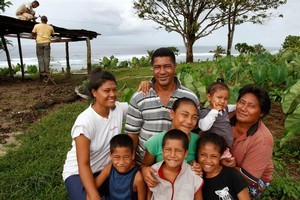 Tui Loli and his wife Faiilagi, with six of their children, who now live on Tsunami St, high above Lalomanu beach. Photo / Brett Phibbs