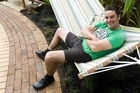 Justin Newcombe enjoys the newly landscaped swimming pool area from his suspended hammock. Photo / Richard Robinson