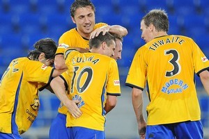 Gold Coast players celebrate with John Curtis after he scored the match-winner against Newcastle. Photo / Getty Images