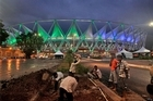 Workers level the ground outside the remodelled Jawaharlal Nehru Stadium. Photo / AP