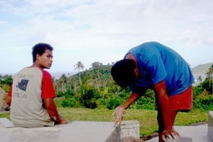 Boys add finishing touches to the newly tiled graves of tsunami victims, in preparation for a memorial on the 29th. Photo / Cherelle Jackson