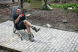 Justin Newcombe enjoys a brew after finishing laying a paving area at Waterview Primary School. Photo / Sarah Ivey