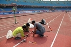 Workers mend the athletics track damaged in the opening ceremony. Photo / Getty Images.