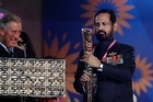 Prince Charles, left, reacts as Suresh Kalmadi holds the Queen's Baton during the opening ceremony. Photo / Saurabh Das.