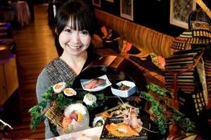 Waitress Noriko Yoshizumi holds the sushi and sashimi platter on the menu at Industry Zen restaurant. Photo / Babiche Martens