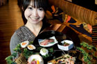 Waitress Noriko Yoshizumi holds the sushi and sashimi platter on the menu at Industry Zen restaurant. Photo / Babiche Martens