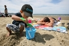 Chance Albert, 3, builds a sandcastle at Orewa Beach while his dad, Geffrey Atutolu, enjoys the Labour Weekend sun. Photo / Natalie Slade