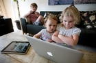 Toby Cotter, 5, with his sisters Evie, 3, and Drew, 2 , are big fans of their dad's iPhone, iPad and Apple computer. Photo / Dean Purcell