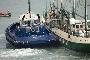 A tug pushes the Rainbow Warrior II away from the coal ship Hellenic Sea during the 2008 protest. Photo / Simon Baker.