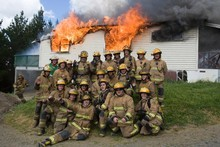 The firefighters pose for a 'team photo' before fighting the flames as part of a training exercise. Photo / Paul Estcourt