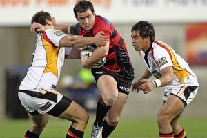 Ryan Crotty of Canterbury is tackled by Trent Renata of Waikato. Photo / Getty Images