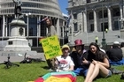 Protestors rally on the grass outside Parliament in Wellington to promote cannabis law reform. Photo / NZPA