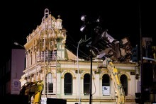 Wrecking machines pull huge blocks of the Palace Hotel down into Victoria St West as demolition of the historic city
