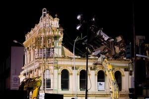 Wrecking machines pull huge blocks of the Palace Hotel down into Victoria St West as demolition of the historic city pub starts early this morning. Photo / Dean Purcell