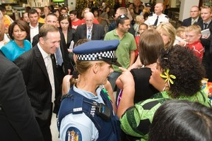 A police officer stops Matt McCarten support Rima Taraia from getting too close to the PM. Photo / Christine Cornege