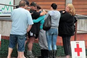 Waiting families gather outside the support centre in Greymouth. Photo / Doug Sherring
