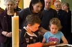 Churchgoers light candles during a special service for the trapped miners at the Holy Trinity Anglican in Greymouth. Photo / Mark Mitchell