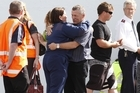 Grey District Mayor Tony Kokshoorn hugs a police officer as distraught family members leave after being told of the second blast. Photo / Mark Mitchell