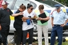 Joanne Alualu (in white t-shirt) is comforted as her brother's body is recovered from the water. Photo / Brett Phibbs