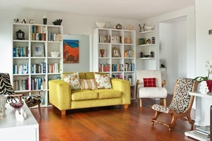 Storage units filled with books, photos and collectables inject more colour into the living room. Photo / Emily Andrews