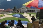 Verdant mountain peaks form a dramatic backdrop to Sapa's main square. Photo / Rob McFarland