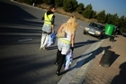 Two prostitutes wear reflective vests as they walk along a road in Lleida, Spain. Photo / Getty Images.
