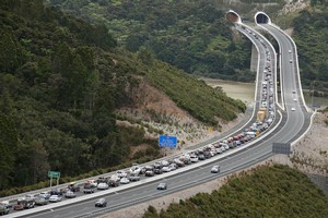 Holidaymakers queue in the northbound lanes of the Northern Gateway toll road yesterday afternoon as they wait to merge from two lanes into one before going through the Johnstone's Hill tunnel. Photo / Brett Phibbs