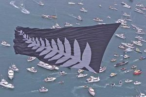 A giant silver fern flag flies over spectator boats following a victorious Team New Zealand back to base in 2000. Photo / Brett Phibbs