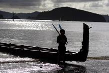 A young crew member stands guard over the waka Hinemoana from Whakatane at Waitangi. Photo / Richard Robinson 