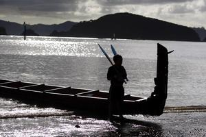 A young crew member stands guard over the waka Hinemoana from Whakatane at Waitangi. Photo / Richard Robinson