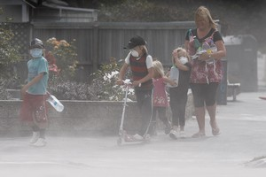 Wendy MacFarlane and her children mask up against wind- whipped dust laden with sewage. Photo / Brett Phibbs