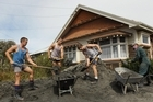 People work to clear away silt caused as a result of liquefaction following the earthquake. Photo / Getty Images
