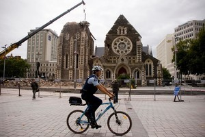 A police officer rides past the damaged Christchurch Cathedral. Photo / Dean Purcell
