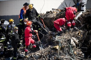 China USAR members assist NZ USAR members as they slowly search through the rubble of the CTV Building. Photo / Dean Purcell