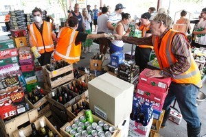 Earthquake-damaged stock is sold outside a liquor store in New Brighton. Photo / Brett Phibbs