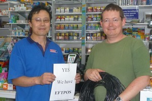 Don Gould (right) helped dairy owner Peter Qu by rigging up a replacement Eftpos line. Photo / Supplied