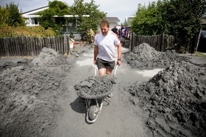 Crusaders rugby player Kieran Read helps with the clean up. Photo / Dean Purcell