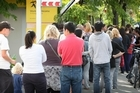People queue outside the Work and Income offices on Riccarton Rd in Christchurch after last Tuesday's earthquake. Photo / Greg Bowker