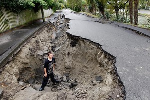 Tristan Webb stands in a large hole along River Road, Avonside, Christchurch. Contractors Fulton Hogan say billions will be needed to rebuild Canterbury's roading infrastructure. Photo / Getty