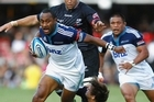 Blues wing Joe Rocokoco looks for a way through the defence as an anxious Kevin Mealamu supports him. Photo / Getty Images