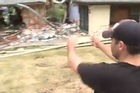 Troy Laffey shows where a boulder tore through one of the homes.